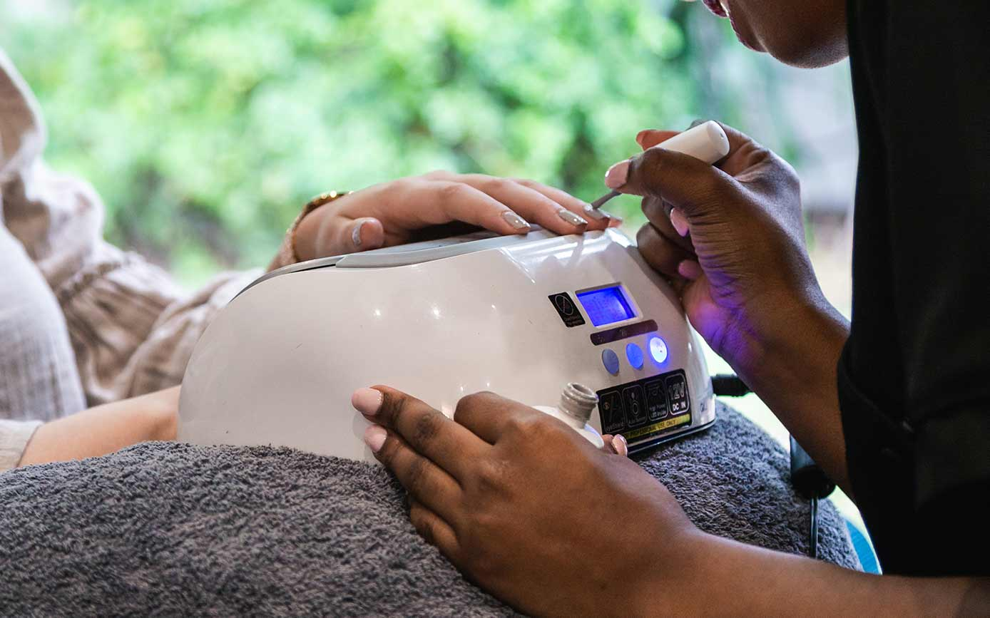Beauty therapist applying Gelish manicure