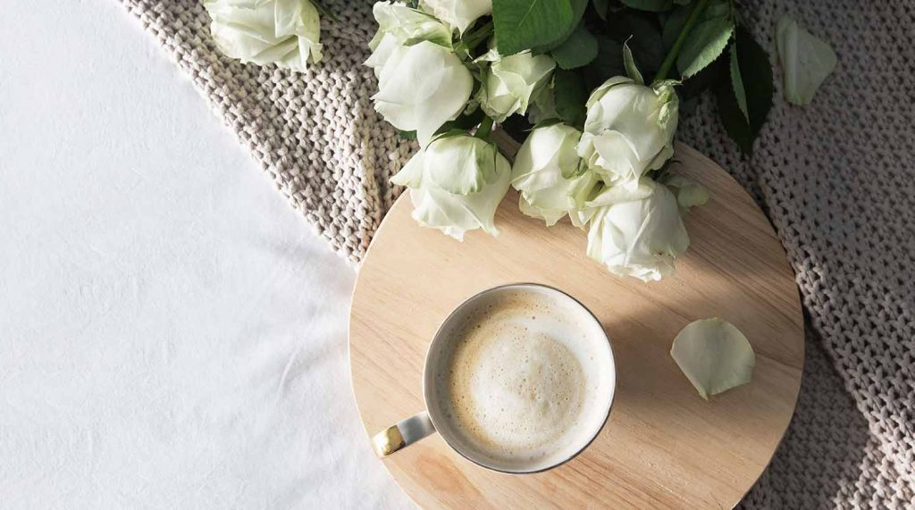 White roses and cup of coffee flat lay