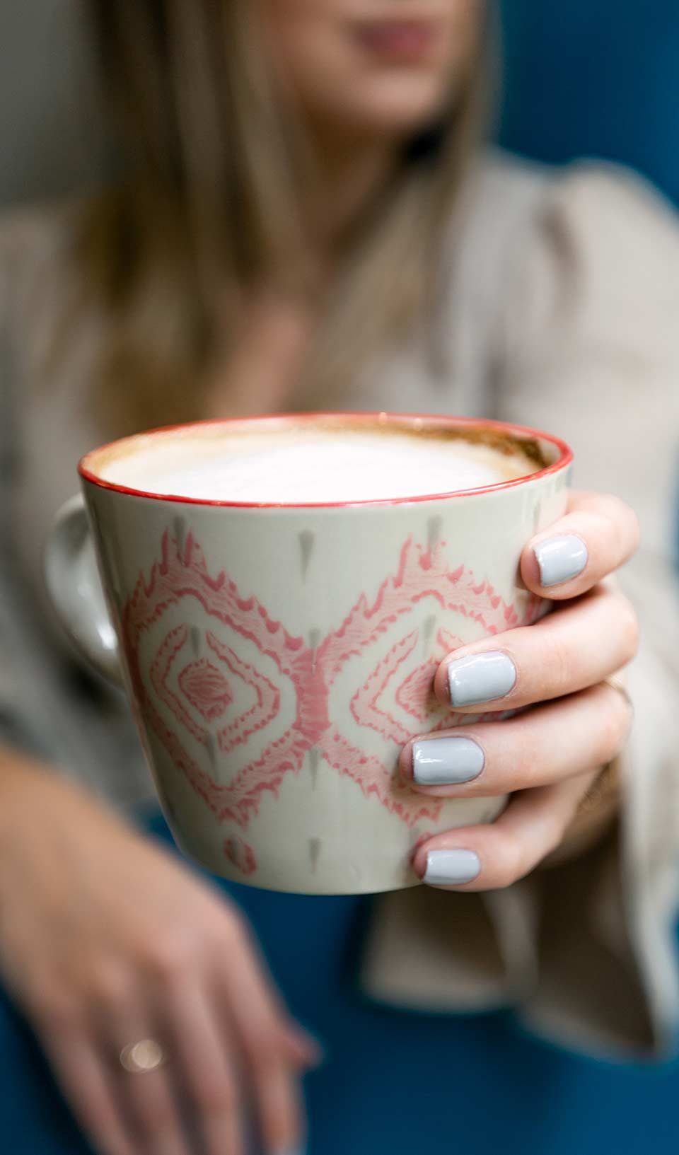 Painted nails holding cup of coffee